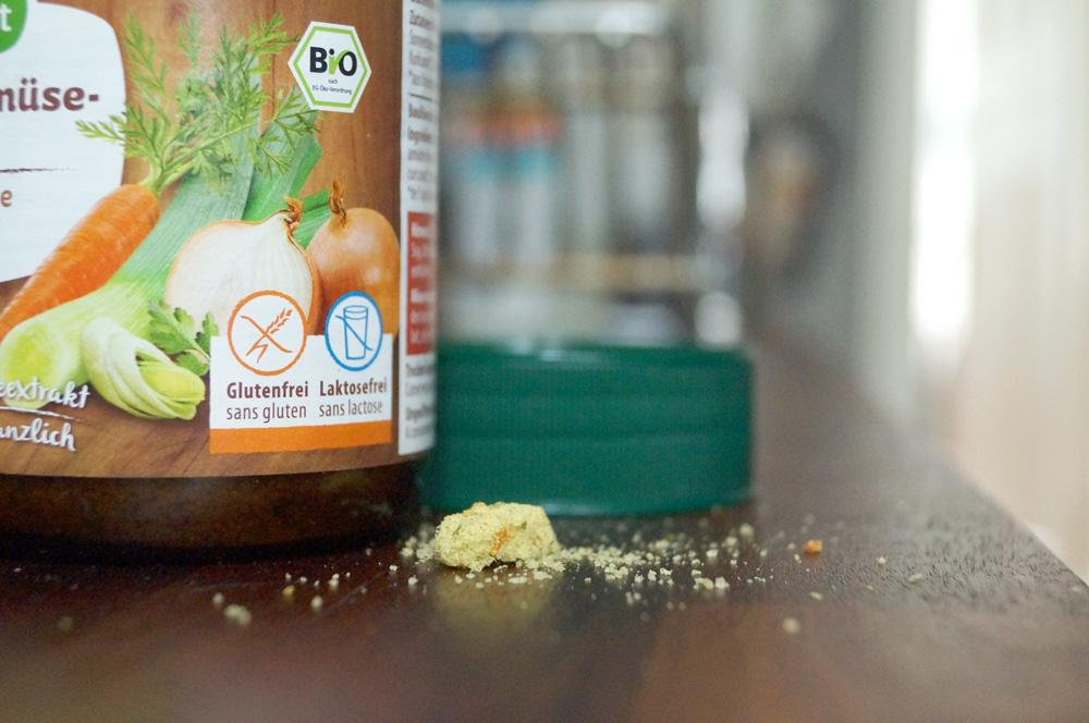Ein Glas mit glutenfreier Gemüsebrühe, davor einige Krümel