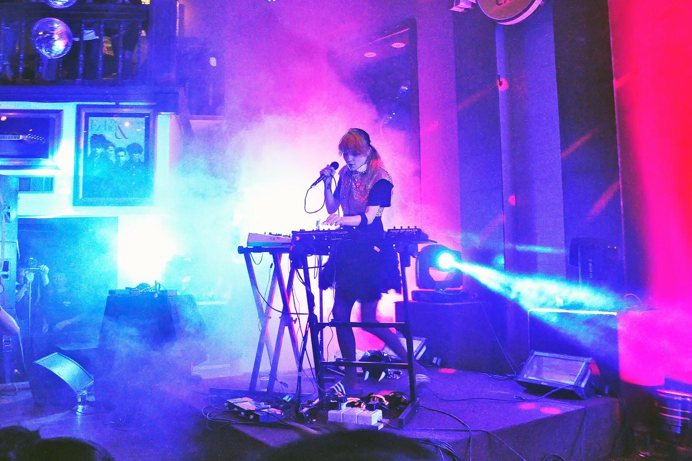Die Musikerin Grimes allein auf einer Bühne, mit Mikrophon und zwei elektronischen Tasteninstrumenten, in Kunstnebel und Scheinwerferlicht.