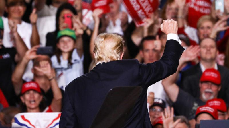 Donald Trump mit dem Rücken bei einer Wahlkampfveranstaltung zur Kamera vor Unterstützer*innen